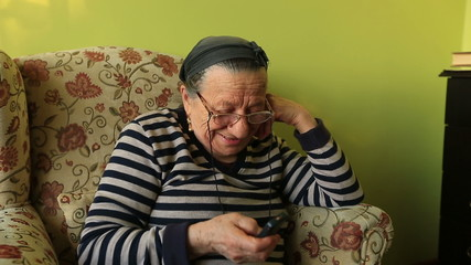 elderly woman talking on the mobile phone at home