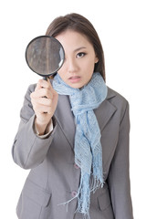 asian woman looking through a magnifying