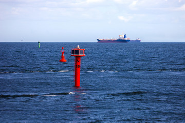 Cargo ship and buoy at sea.
