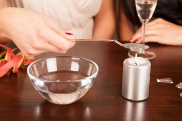 Damenhand hält Löffel für Bleigießen über Kerze