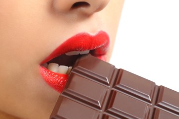 Beautiful woman red lips eating chocolate