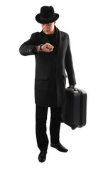 Man with suitcase is checking time on watch