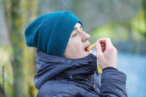 Teen eating french fries in the park