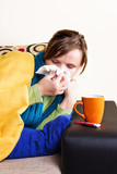 Young woman having flu, blowing her nose