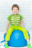 Happy boy doing gymnastics on blue ball.