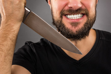 Closeup portrait of a threatening man with beard holding a knife