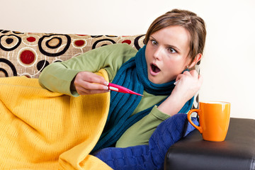 Expressive young woman having flu and checking thermometer