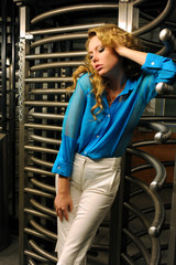 Redhead model posing by entrance with revolving door