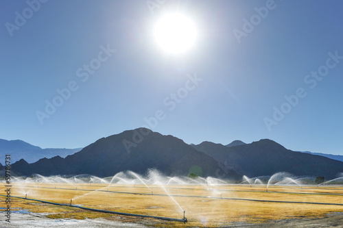 Irrigation sprinklers water a dry field by mountains