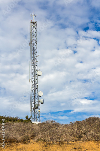 Cell phone telecommunication tower, blue sky clouds background