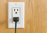 Electrical outlet with black power cord on wood grain wall