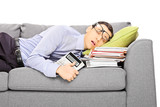 Exhausted young businessman sleeping on a couch with documents
