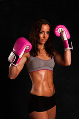 A sweaty fit woman kickboxer ready for exercise