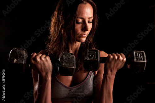 A sweaty fit attractive woman doing barbell curls