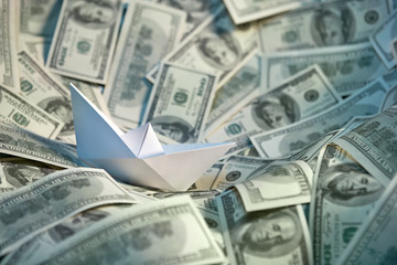 Paper ship floating on the sea of money
