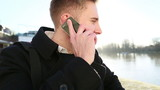 Handsome man talking and smiling on a phone outdoors