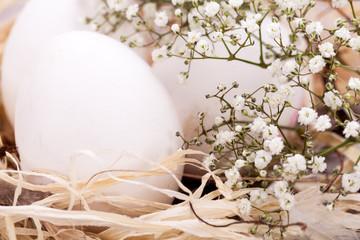 weisse eier mit blüten im nest aus stroh ostern dekoration