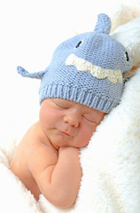 smiling newborn baby in shark hat