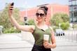 junge attraktive frau mit sonnenbrille smartphone und coffee to