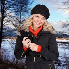 Lächelnde junge Frau in einer Winterlandschaft