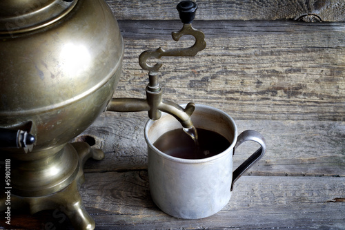 Old retro cup of tea with samovar on vintage table