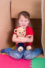 Weinender Junge mit Teddybär