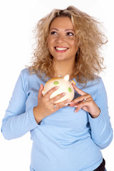 Glückliche junge Frau mit Sparschwein in der Hand