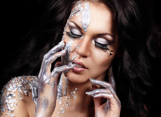Closeup portrait of brunette in liquid silver paint