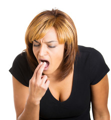 Young woman sticking fingers in her throat, about to vomit