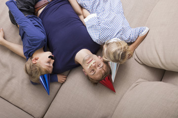 High angle view of father and children with artificial mustache and party hat sleeping on sofa bed