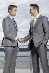 Businessmen shaking hands on terrace against sky