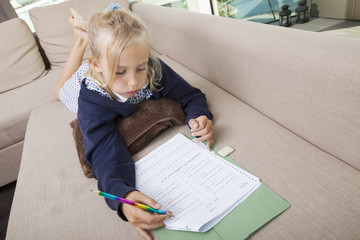 Little girl solving mathematics sums on sofa