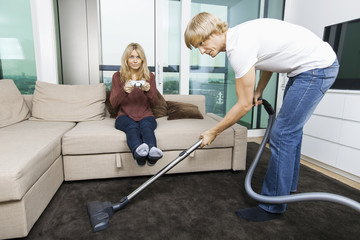 Man vacuuming while woman play video game in living room at home
