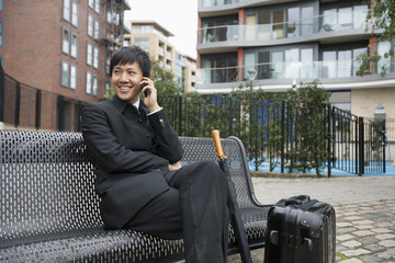 Happy mid adult businessman with luggage using cell phone on bench