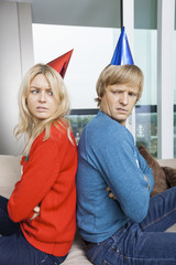 Side view of annoyed couple in Christmas sweaters and party hats sitting back to back at home