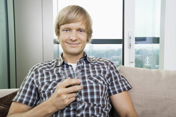 Portrait of smiling mid-adult man with glass of drink on sofa at home
