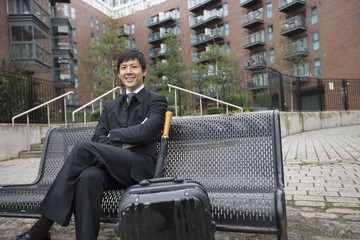Portrait of confident businessman with luggage sitting on bench against buildings