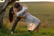 Two sweethearts kissing under tree on field