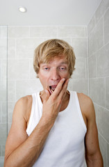 Portrait of tired man yawning in bathroom