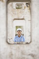 Portrait of male architect through pillars at construction site