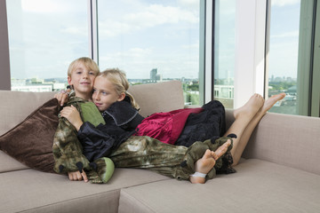 Affectionate siblings in dinosaur and vampire costumes at home