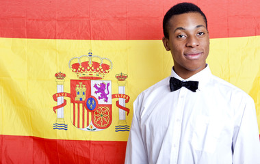 Close-up portrait of young man against Spanish flag