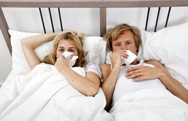 Portrait of couple suffering from cold lying on bed