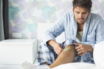 Man looking at wound on bed at home