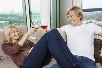 Happy relaxed couple toasting wine glasses in living room at home