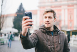 Man taking self portrait in the city with mobile phone