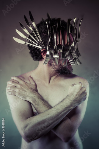 Nude man with helmet made ​​with forks and knives, artistic