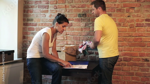 worried couple looking at contract of buying flat