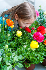 Little girl smelling flowers in flower shop