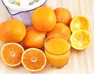 Glass of orange juice, peel, oranges and juicer.